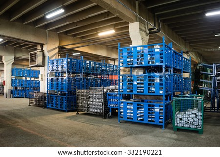 view of an industrial hall, with big blue, green, and grey metallic bins, containing different elements which make up exhaust pipes and accessories - stock photo