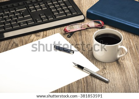 View Of An Office Desk With Keyboard, Calendar, Coffee Cup, Sheet Of Paper For Notice, Glasses And Fountain Pen.