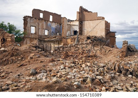 View of an old ruined house over a pile of rubble. House in ruins. - stock photo