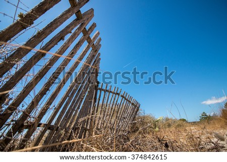 View of an old wood fence to hold sand dunes on the Algarve, Portugal. - stock photo