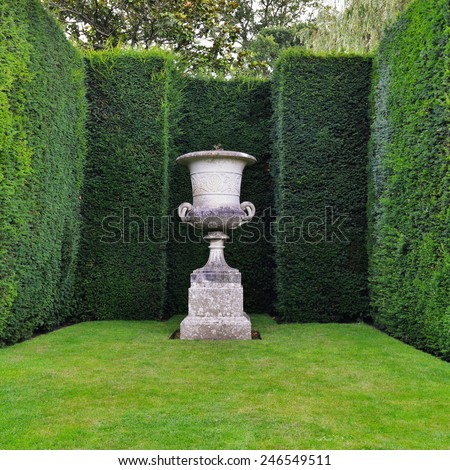 View of an Ornamental Stone Vase, Lush Lawn and Sculpted Hedge Topiary in a Beautiful Garden - stock photo