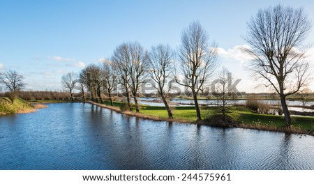 View of an picturesque  Dutch landscape in winter in low afternoon sunlight - stock photo