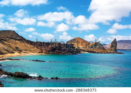 View of an underwater crater in the foreground with Pinnacle Rock in the background on Bartolome Island in the Galapagos Islands - stock photo