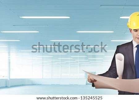 view of architect looking comparing housing project on blue blurred background - stock photo