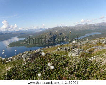 View of arctic Kilpisjarvi lake from the sacred Saana mountain, Lapland, Finland (at the border with Norway); rocks and cotton grass on the foreground - stock photo
