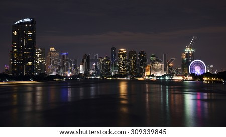 View of Asiatique and Modern buildings along Chao Phraya river at night in Bangkok, Thailand - stock photo