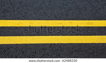 view of asphalt with distinct two yellow stripes - stock photo