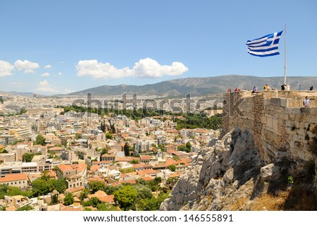View of Athens, Greece from the Acropolis with Greek flag in the background - stock photo