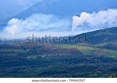 View of atmospheric air pollution from factory in countryside - stock photo