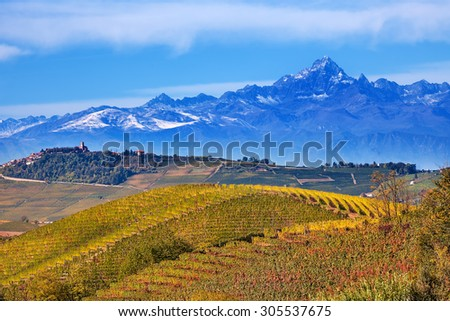 View of autumnal hills and vineyards with mountains on background in Piedmont, Northern Italy.