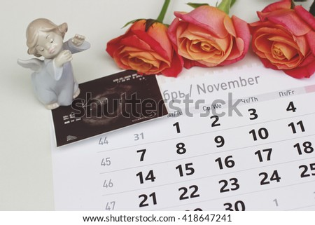 View of baby ultrasound scan/photo on the calendar with an angel and three pink roses on it - stock photo
