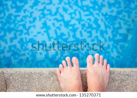 View of bare male feet at swimming pool side - stock photo