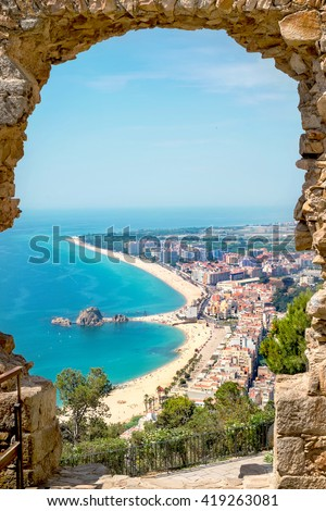 View of beach and village Blanes through a stone arch of the St. John Castle. Costa Brava , Span - stock photo
