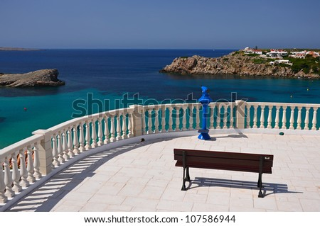 View of beautiful bay at Arenal D'en Castell from white terrace with rest bench, Menorca, Balearic Islands, Spain