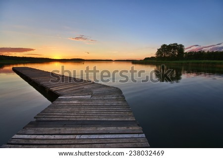 View of beautiful calm lake during sunset, Mazury, Poland - stock photo
