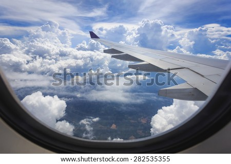 View of beautiful cloud and wing of airplane from window - stock photo