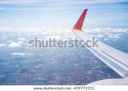 View of beautiful clouds and wing of airplane from window, view of through window aircraft during flight in wing with a nice blue sky - stock photo
