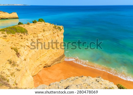 View of beautiful sandy beach and turquoise sea in Armacao de Pera village, Algarve region, Portugal - stock photo