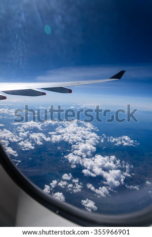 View of beautiful sunny clouds and wing of airplane from Window. Travel, Transportation and Tourism background. Business, Holidays and Vacations publications. Freedom concept