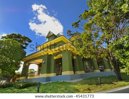 View of beautiful tropical residence painted in green against blue sky - stock photo