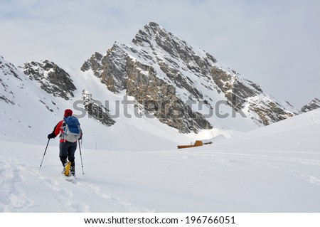 View of beautiful view of Carpathian mountains with snowshoeing tourist in the foreground.