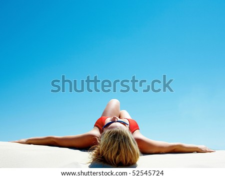 View of beautiful woman lying on the sand getting pleasure - stock photo