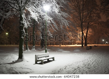 View of bench and shining lantern. Night shot.