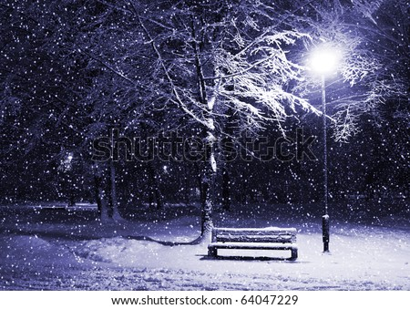 View of bench and shining lantern through snowing. Blue tone. Night shot.