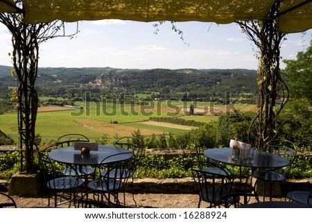 View of Beynac Castle in the Dordogne valley, France, with cafe tables and chairs set out on the terrace in the foreground