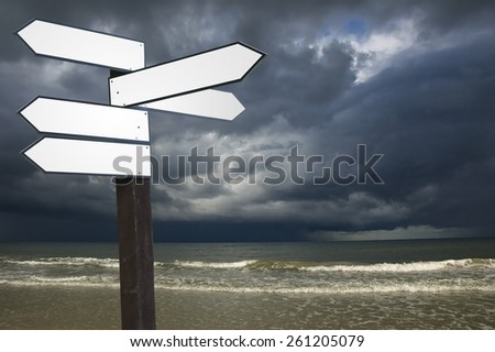 View of blank wooden multi-direction guidepost with dark stormy sky over Baltic Sea water, Poland