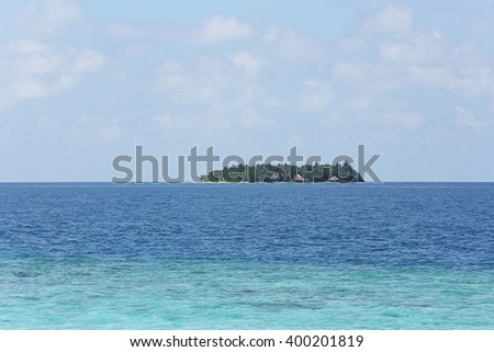 View of blue clear ocean water and tropical island on horizon - stock photo