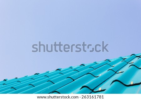 View of blue roof tiles and blue sky background. - stock photo