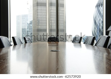 view of boardroom table with chairs and city buildings in background - stock photo