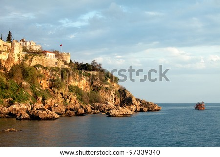 View of boat heading along the coastline in Kaleici, Antalya, Turkey. - stock photo