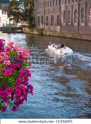 View of boat on canal. Hanging basket of flowers suspended on the hand-rail of canal in Ghent (Gent), Belgium. - stock photo