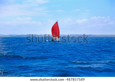 View of boat with red sail at the harbour in Russell,  Bay of Islands, New Zealand