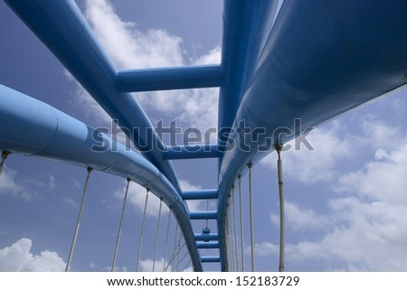 View of bridge support against a blue sky - stock photo