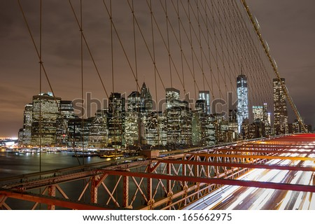 View of Brooklyn Bridge with traffic and Manhattan skyline by night