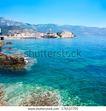 View of Budva Old Town with Clear Blue Water in Foreground. Montenegro, Balkans, Adriatic Sea. European Summer Resort in Mediterranean. Copy Space. - stock photo