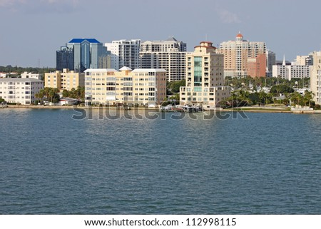 View of buildings on the edge of  Sarasota Bay, Sarasota, Florida from the water with palm trees and a blue sky. - stock photo