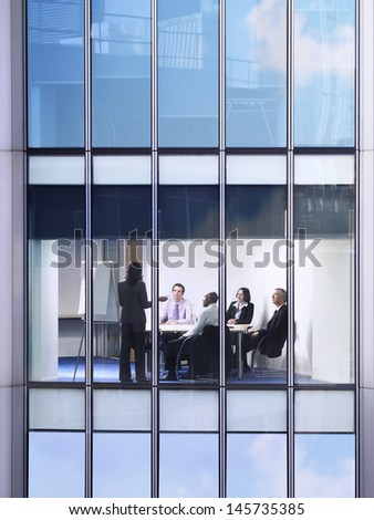View of business people in conference room through window - stock photo