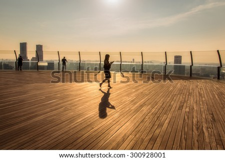 view of business people walking on top view tower at sunset time. - stock photo