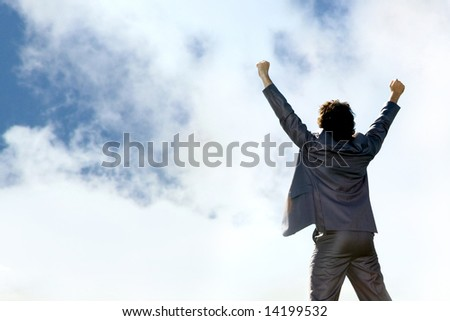 View of businessman standing a back raising his hands on the background of sky - stock photo