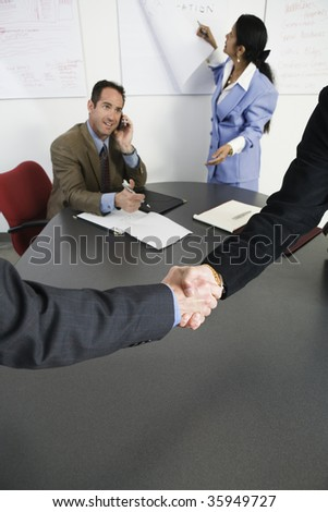 View of businessmen shaking hands in an office. - stock photo
