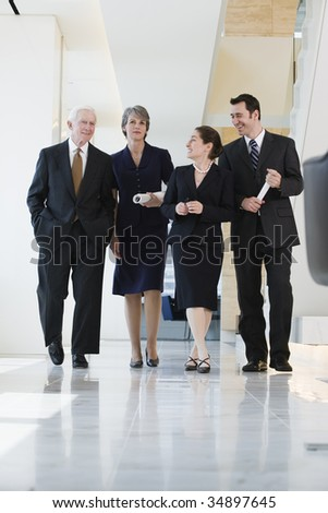 View of businesspeople walking in a corridor. - stock photo