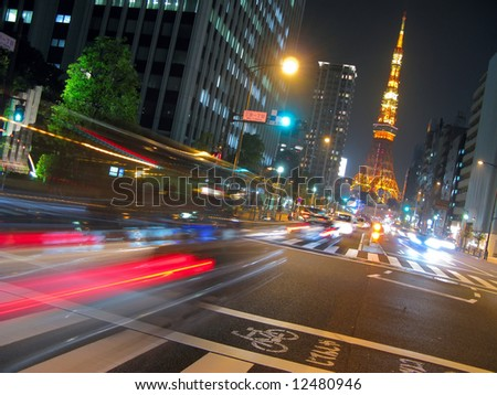 View of busy street at night with Tokyo Tower in the distance.  Tokyo, Japan.