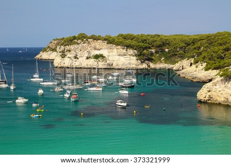 View of Cala Galdana Beach with turquoise waters and some boats. Balearic Island.  View of Cala Galdana beach. Menorca, Balearic Islands, Spain - stock photo