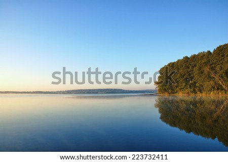 View of calm foggy water surface just after sunrise, Mazury, Poland - stock photo