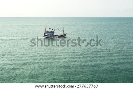 view of calm sea horizon and single fisherman. antique profession concept - stock photo