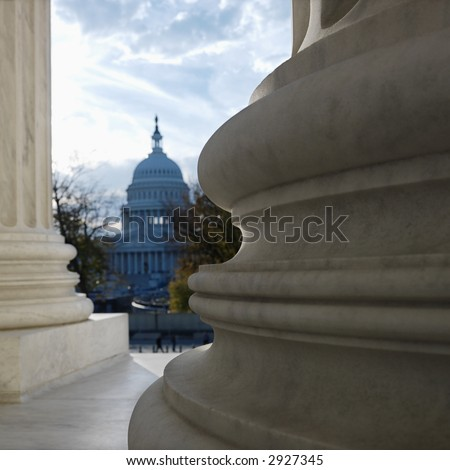 View of Capitol building in distance from behind columns of the Supreme Court building in Washington D.C. - stock photo